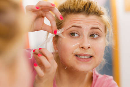 Facial dry skin and body care, complexion treatment at home concept. Woman removing gel peel off mask from face