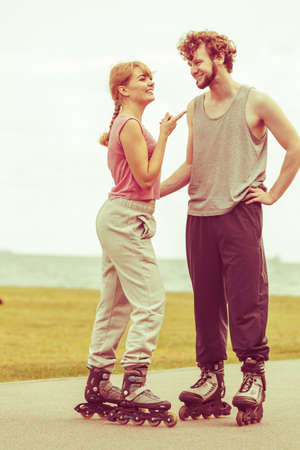 Active holidays, exercises, relationship concept. Woman and man wearing rollerskates standing and looking at each other, girl pointing at him