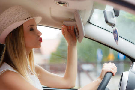 Distracted driver. Young attractive woman looking in mirror while driving the car.