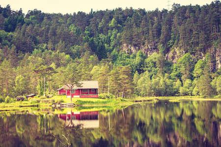 Wooden cabin hytte in norwegian green forest on water lake shore. Beautiful landscape in Norway, Scandinavia