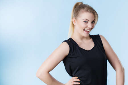 Happy woman wearing black tank top smiling having good mood. Sporty outfit