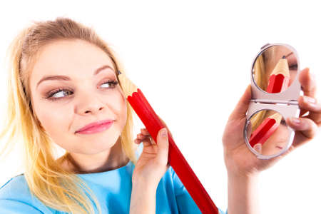 Funny silly woman trying to paint her eyebrows using big huge oversized regular student pencil. Make up fun concept. Reklamní fotografie