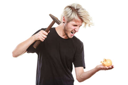 Money, savings, finances concept. Angry sreaming young blonde man wearing black t shirt trying to break piggy bank with hammer, studio shot isolated Stok Fotoğraf