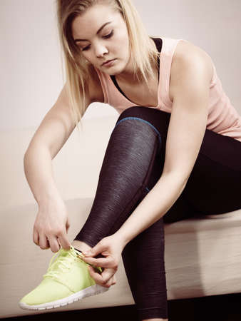 Young blonde woman in sportswear sitting on sofa indoor getting ready for exercises. Tying up shoes