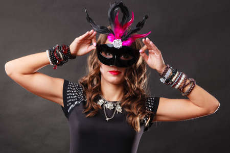 Holidays, people and celebration concept. Woman with carnival venetian mask on dark background.
