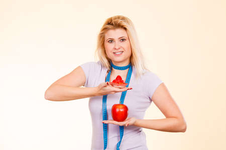 Diet, sweets temptation, healthy choices concept. Woman with measuring tape around her neck choosing between apple and sweet cupcake making decision.