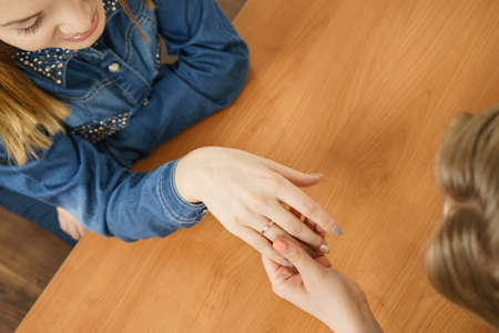 Woman showing her female friend engagement ring sharing great news. Family beginnings concept.