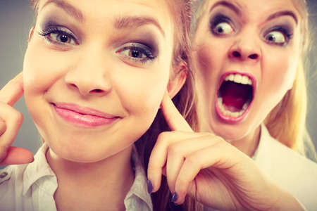 Conflict, bad relationships, friendship difficulties. Two young women having argument. Angry fury girl screaming at her friend or younger sister, female closing his ears, not listening Stock Photo