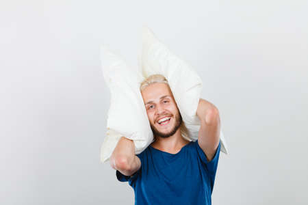 Sleeping well concept. Happy young man rested after good night sleep playing with pillows, smiling having fun Stok Fotoğraf