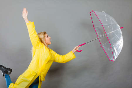 Rainy autumn day accessories ideas concept. Shocked woman holding opening clear transparent umbrella fighting with wind.