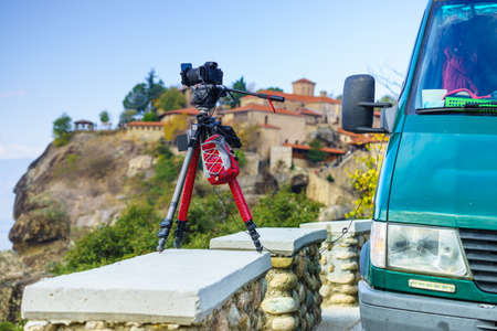 Professional camera on tripod taking picture film video from Meteora monasteries, Greece Kalambaka. Banco de Imagens