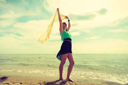 Summertime, happiness, stress free concept. Woman wearing short colorful dress running with shawl in her hand on beach having fun
