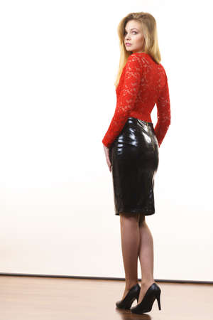 Sexy adult pretty woman wearing seductive outfit, leather latex slim skirt and red lace top.