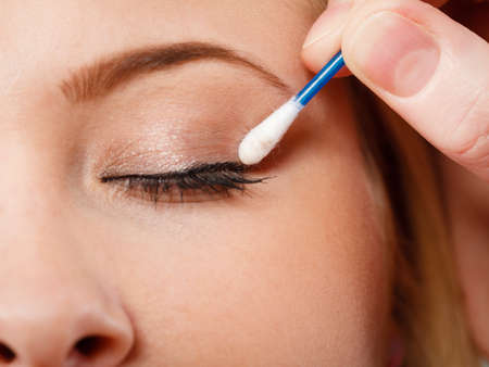 Visage, beauty concept. Closeup portrait of woman face getting her eye makeup done with cotton buds Stock Photo