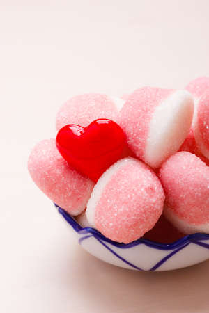 Sweet food candy. Pink jellies or marshmallows with sugar in bowl on wooden table decorated with red heart love symbol