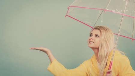 Blonde woman wearing yellow raincoat holding transparent umbrella checking weather if it is raining. Stock fotó - 102994111