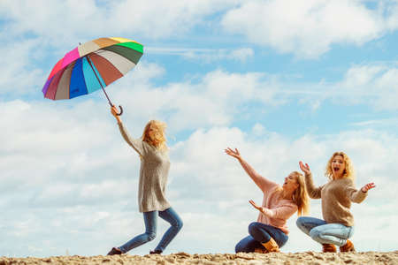 Three women full of joy having great time together. One woman holding colorful umbrella. 版權商用圖片 - 114909325