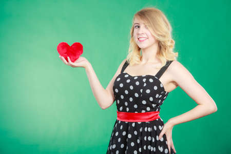 Woman blonde cute girl wearing dotted dress holding red heart love symbol studio shot on green. Valentines day happiness concept Stock Photo