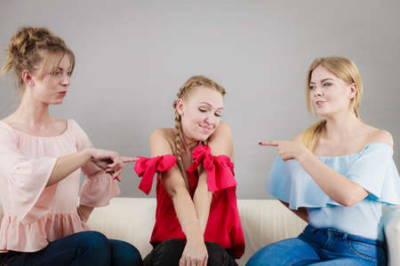 Two woman pointing at her female friends accusing for something she have not done.