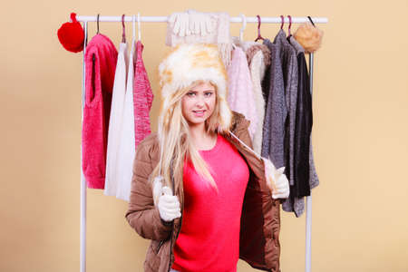 Accessories and clothes for cold days, fashion concept. Blonde woman in winter warm furry hat and jacket, standing in wardrobe thinking what to wear