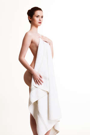 Beauty of female body, showering, clean and fresh skin concept. Naked woman in towel after bath. Studio shot isolated