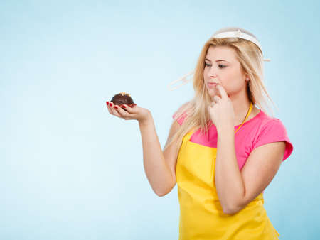 Baking tasty desserts sweets at home concept. Woman holding delicious sweet chocolate cupcake wearing apron and colander on head as hat, thinking