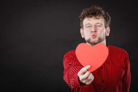 Amore e aiuto dalle persone. L'affascinante uomo adorabile con il cuore di carta rosso persuade ad essere un buon utile, fiducioso. San Valentino o concetto di beneficenza.