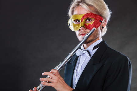 Holidays, people and celebration concept. Elegant young guy wearing suit white shirt bow tie and carnival venetian mask playing flute instrument on dark