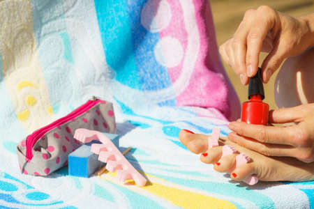 Woman relaxing doing her pedicure with red nail polish on beach towel. Female taking care of feet Stockfoto