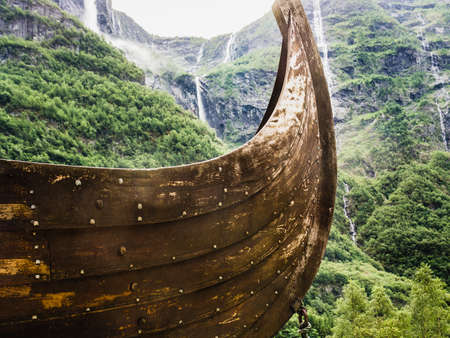 Part of old wooden viking boat in norwegian nature, mountains with waterfalls in the background. Tourism and traveling concept