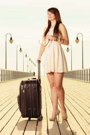 Travel, packing, journey concept. Woman wearing white short dress standing next to her suitcase thinking about adventure, pier in background.