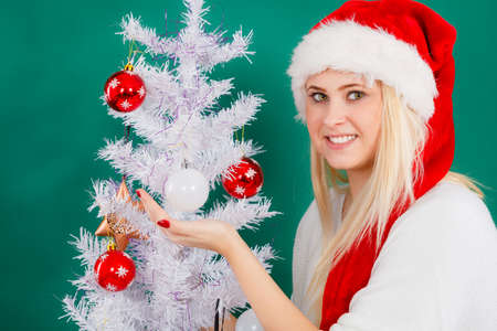 Cozy holiday interior, seasonal accessories concept. Blonde young woman in Santa hat decorating Christmas tree
