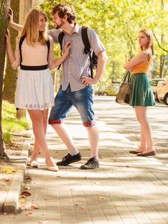 Chica celosa mirando pareja coqueteando al aire libre. Feliz pareja de hombre y mujer joven que data. Asunto de romance de verano. Foto de archivo