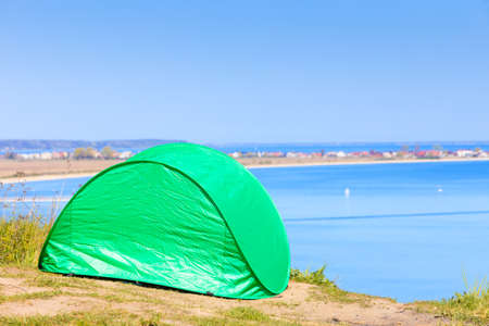 Tourism and recreation. Small green tent in natural area surrounded by meadow water sea lake.