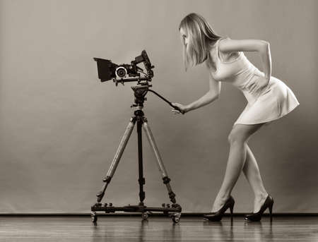 Attractive fashionable blonde woman in full length taking photos with camera black