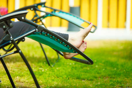 Female bare feet. Woman relaxing on sunbed or deck chair in her garden during sunny weather. Standard-Bild