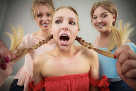 Woman being bullied by her two female friends. Friendship rivaly and envy problems. Banco de Imagens - 107340096
