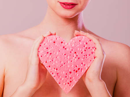 Skin care hygiene body treatment concept. Close up woman naked shoulders smooth skin holding pink heart shaped sponge in hands. Stock Photo