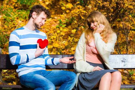 Accepting and sharing feelings. Confessing love and affection with romantic gesture. Positive reaction. Pair sit on bench in park man present plush heart toy to happy girl.