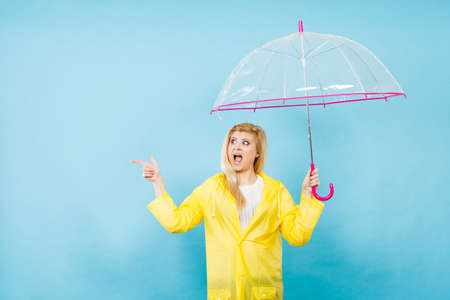 Blonde woman wearing yellow raincoat holding transparent umbrella checking weather if it is raining pointing with finger at copyspace. Banco de Imagens