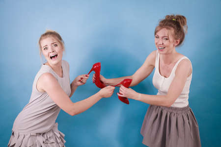 Two women having argue fight for red high heels shoes in shop. Sale shopping madness Standard-Bild