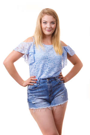 Pretty joyful teen presenting fashion. Young woman wearing stylish blue top and short jeans shorts. 版權商用圖片