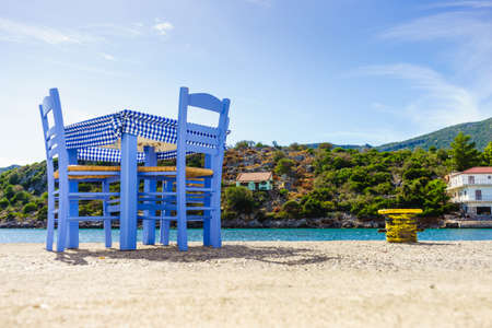 Seaside blue table and chairs open cafe outdoor restaurant in Greece on sea shore. Summer vacation on resort. Editorial
