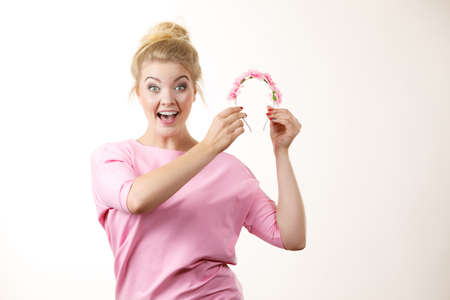 Happy positive cheerful smiling woman wearing pink dress with blonde hair holding flower wreath
