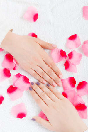 Unrecognizable woman presenting her beautiful painted gel hybrid nails. Nail care concept. Stock Photo