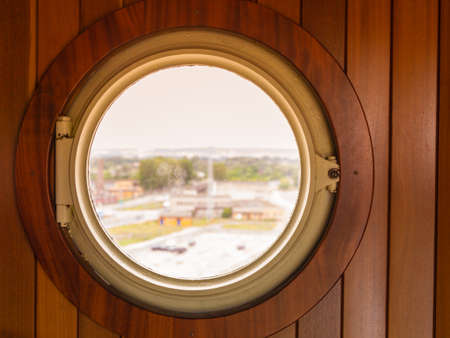 Ship bull's eye, porthole window in wooden wall looking out at port