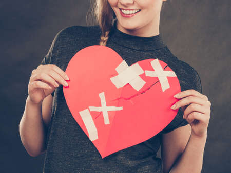 Healed love. Valentines Day concept. Young smiling woman holding big red heart with plaster. Girlfriend healing relationship. Stock fotó - 108764856