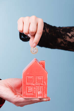 Savings for future plans. People hands with red little house piggy bank and silver coin. Money loin for family home better life. Stock Photo