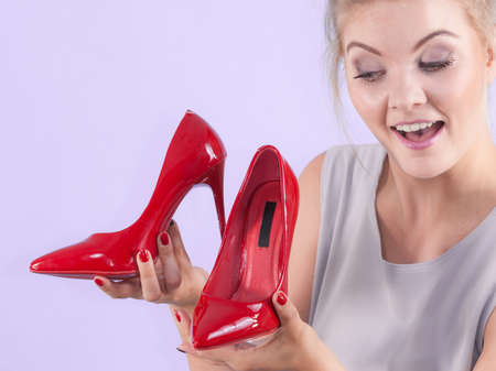 Woman hand fashion stylist presenting her elegant shoes. Beautiful red sensual high heels. Outfit accessories