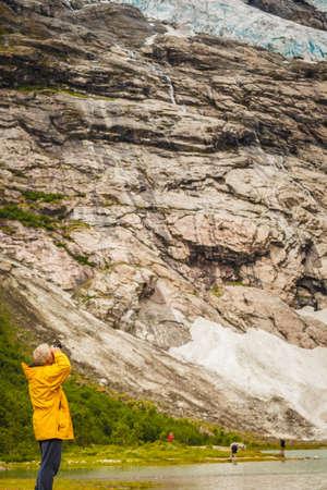 Adventure hiking man admiring Boyabreen Glacier in Fjaerland area, Sogndal Municipality in Sogn og Fjordane county, Norway. Tourist visiting norwegian nature landscape.